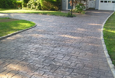 Concrete driveway made to look old and weathered with stamping and staining.