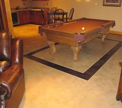 Residential home bar with pool table setting on decorative concrete.