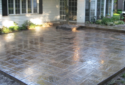 Backyard patio made from concrete that is stamped, stained and made to look like stone pavers.
