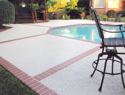 Pool deck with textured concrete and brick stamped edges.