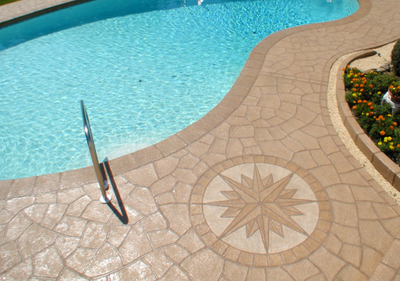 Smooth finished concrete pool deck with compass designed stamped in.