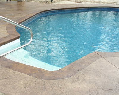 In-ground pool with stamped concrete pool deck.