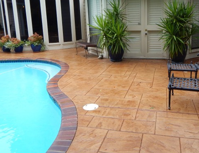 Brown stamped concrete pool surround with brick style edges.